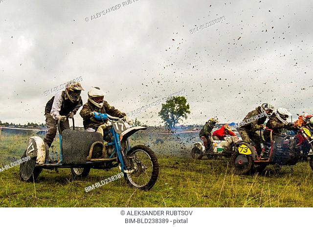 Caucasian racers on motorcycles with side cars spraying dirt