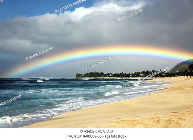 Hawaii, Oahu, North Shore, Beautiful bright rainbow arches over land and sea
