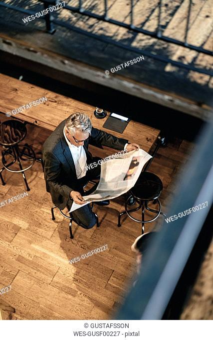 Senior businessman sitting cafe, reading newspaper