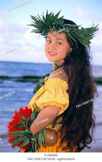Portrait shot, side view of young girl in hula attire on beach smiling, hands C1457 on hips