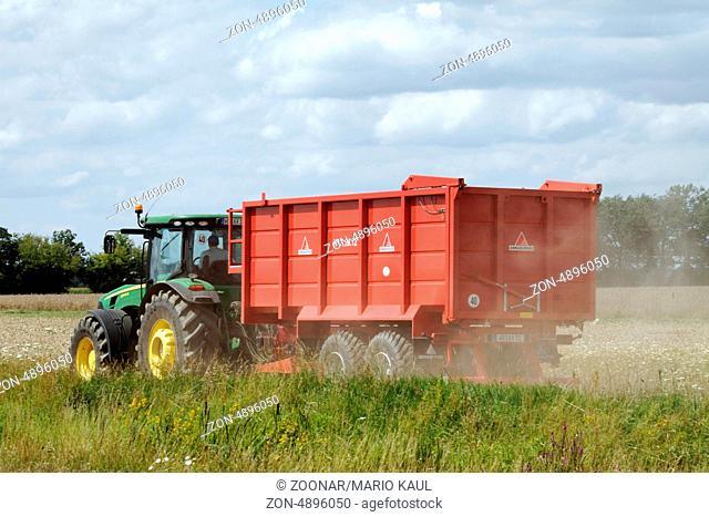 Ein Traktor vom Typ John Deere 8245R mit Anhänger während der Rapsernte auf einem Feld bei Axien in Sachsen - Anhalt