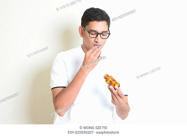 Sick Indian guy eating medicine pill. Asian man standing on plain background with shadow and copy space