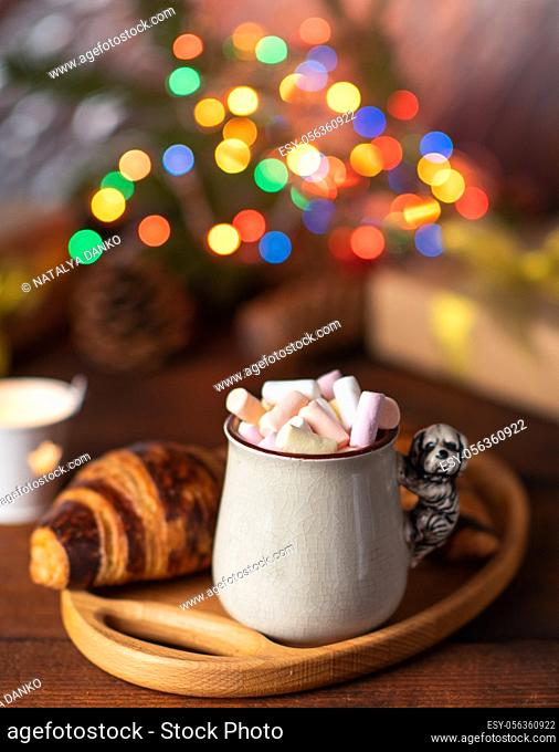 ceramic cup with cocoa and marshmallows and a baked croissant on a brown table, behind Christmas lights