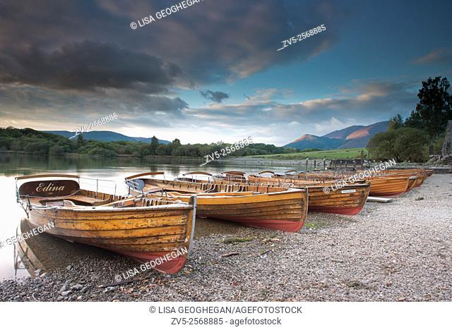 Rowing boats on the shore of Derwent Water near Keswick at sunset, Lake District, Cumbria, England, Uk, Gb