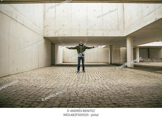 Man with arms outstretched and head back in modern architecture