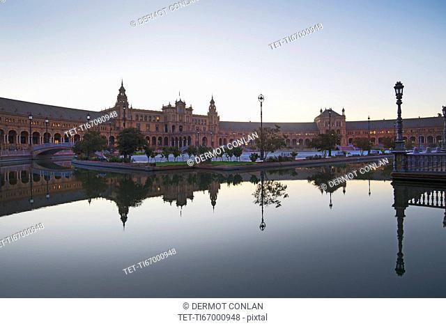 Spain, Seville, Plaza De Espana reflecting in pond at dawn