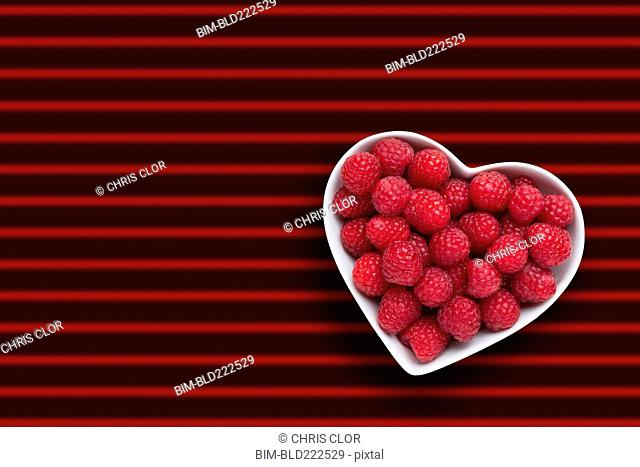 Raspberries in heart-shape bowl on red striped background