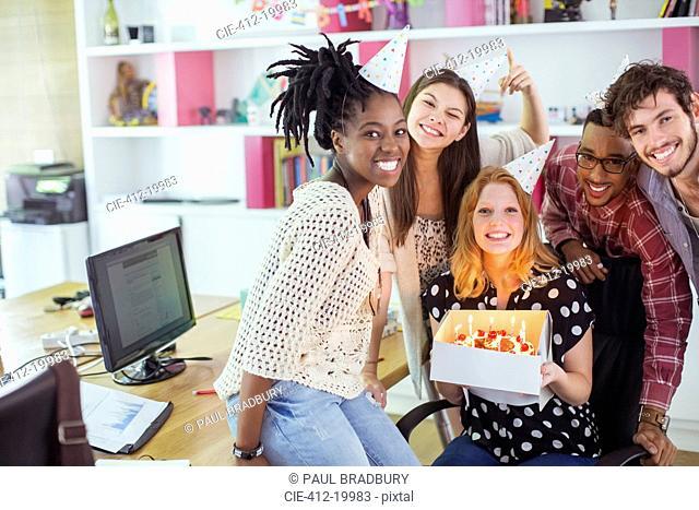 People celebrating birthday in office