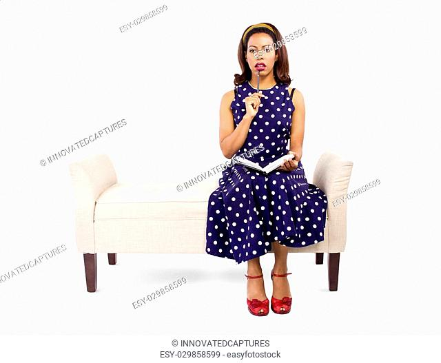 Vintage style black female author writing and sitting on a chaise lounge
