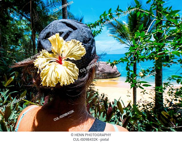 Woman with tropical flower in her hair looking out to a empty beach, Ilha Grande, Rio de Janeiro, Brazil