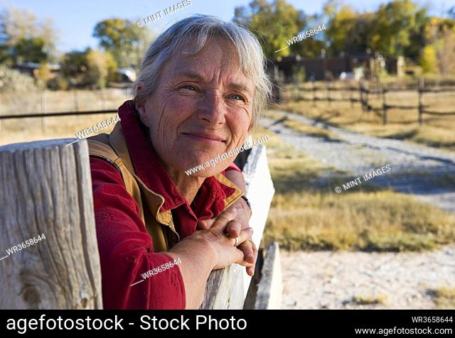 Mature woman at home on her property leaning on a gate