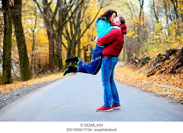 Portrait of young loving couple kissing in autumn park