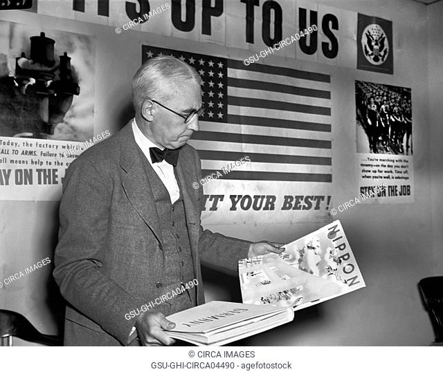 Elmer Davis, Director of Office of War Information, Examining Nazi and Japanese Propaganda Organs at Press Conference to show Material the Axis is Distributing...
