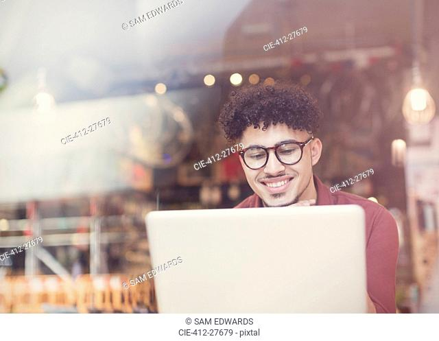 Smiling man with curly black hair using laptop at cafe window