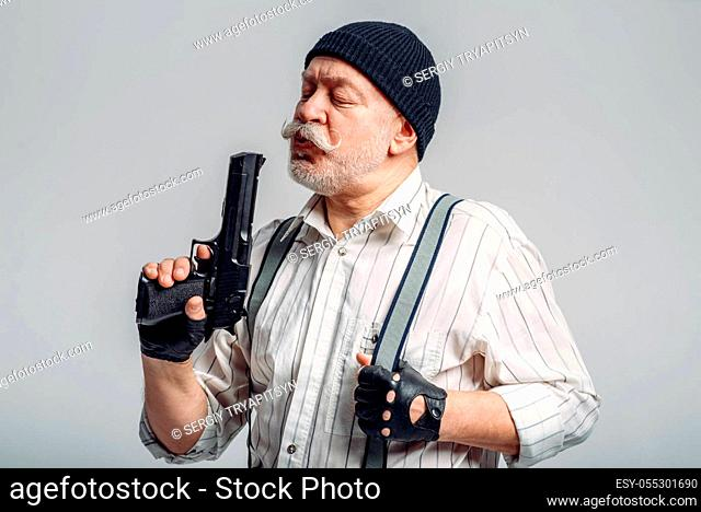 Elderly man with gun isolated on grey background, gangster. Mature senior in hat holds weapon, robber in old age