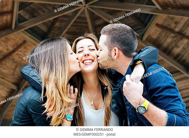 Young woman and a young man kissing and embracing female friend