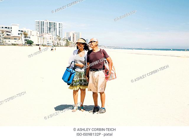 Senior couple walking on beach, carrying bags for picnic, Long Beach, California, USA