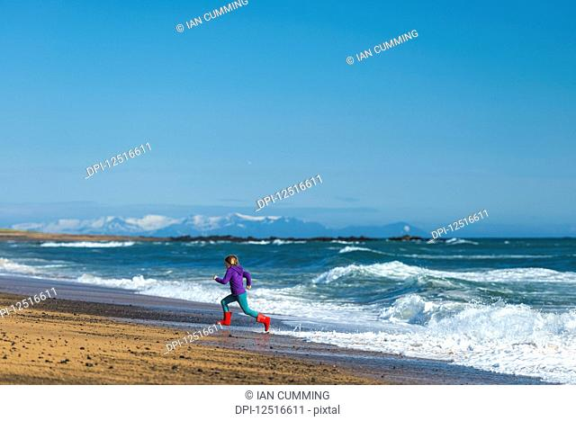 Girl running from waves on Langaholt beach; Langaholt, Iceland