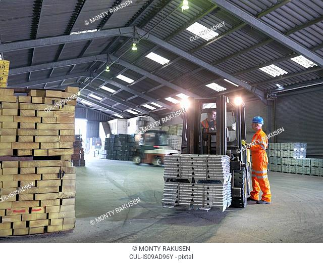 Worker checking delivery of metal alloy with fork lift driver in port store
