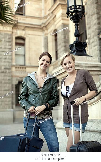 Two young women with wheeled suitcases, Cape Town, South Africa