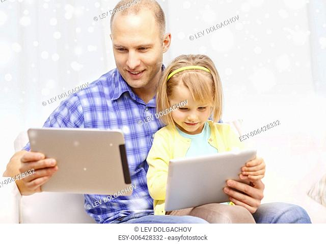 family, children, technology and people concept - happy father and daughter with tablet pc computers at home