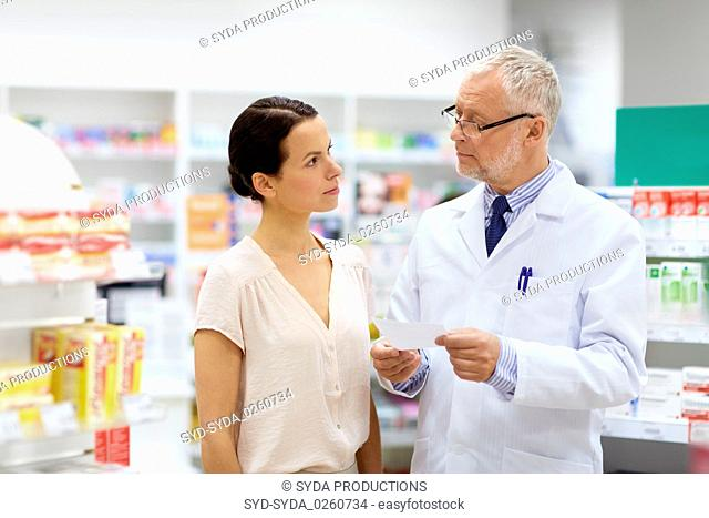 apothecary and woman with prescription at pharmacy