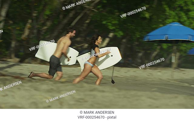 Slow motion wide tracking shot of couple running to ocean on beach / Esterillos, Puntarenas, Costa Rica