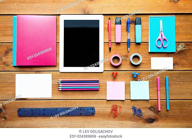 education, school supplies, art, creativity and object concept - close up of stationery and tablet pc computer on wooden table