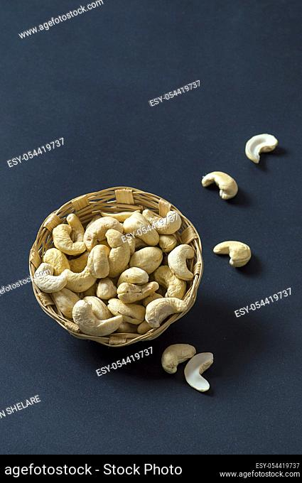 Cashew nuts in basket on black background