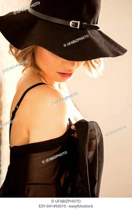 very sexy blond girl, in black bikini lingerie with hat and stocking, sitting in elegant ambient . vintage color