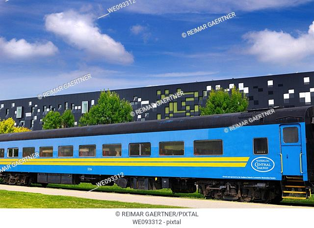 Blue historic Waterloo Central Railway train car with modern Perimeter Institute building