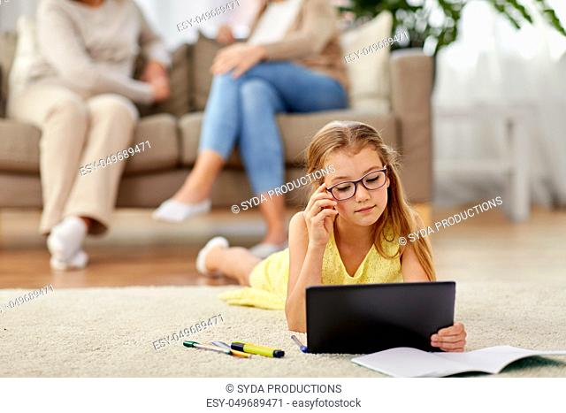 student girl with tablet pc lying on floor at home