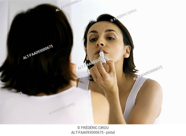 Woman looking in mirror, applying lipstick