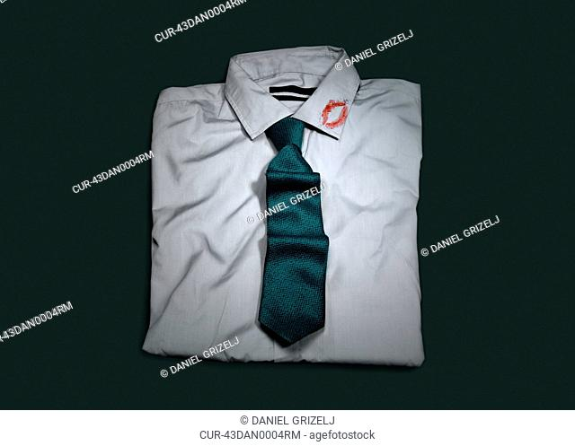 Folded shirt and tie with lipstick kiss