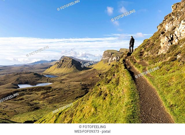 UK, Scotland, Inner Hebrides, Isle of Skye, Trotternish, hiking trail at Quiraing, Loch Cleat, hiker looking at view