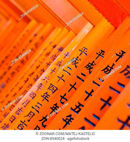 Red wooden Tori Gate at Fushimi Inari Shrine in Kyoto, Japan. Selective focus on traditional japanese writing
