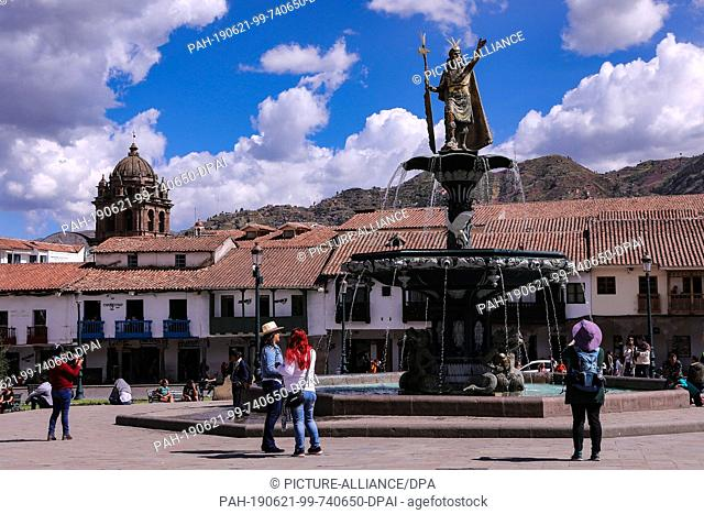 02 May 2019, Peru, Cusco: In the middle of the Plaza de Armes is the Pachacuti fountain. In the background there are churches and old houses
