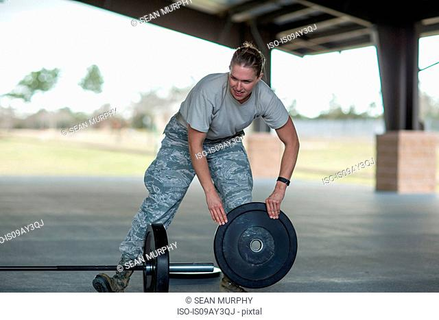 Female soldier preparing barbell for training at military air force base