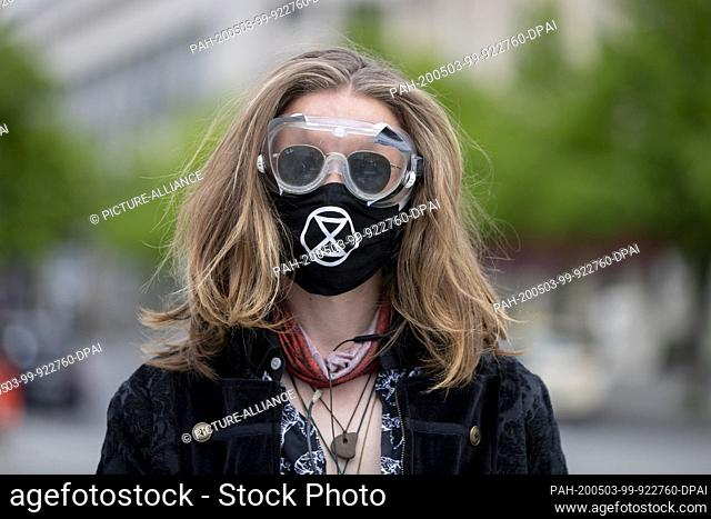 03 May 2020, Berlin: Paul is standing in front of a rally of Extinction Rebellion with mask and goggles at the Brandenburg Gate