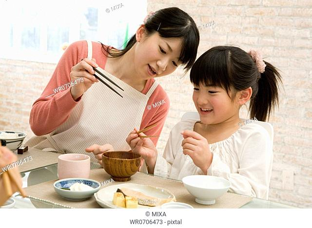 Mother teaching daughter how to use chopsticks