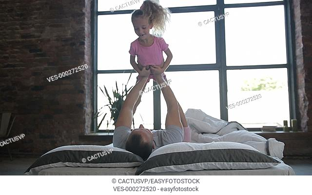Playful father lifting his daughter on bed at home