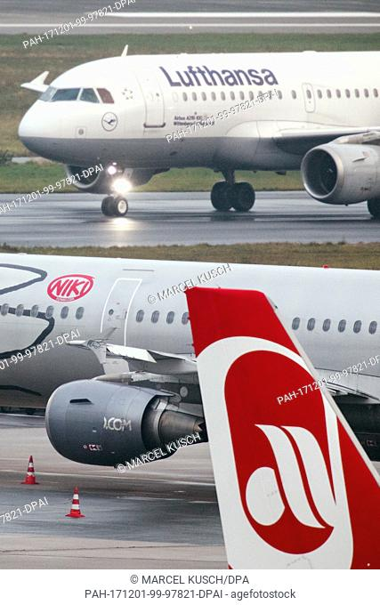 A plane of the airline Lufthansa rolls along the runway past planes of the airlines Niki and Air Berlin at the airport in Duesseldorf, Germany, 1 December 2017