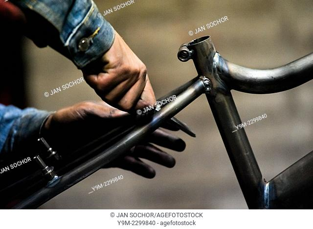A bicycle worker grinds a recently welded bike frame in a small scale bicycle factory in Bogota, Colombia, 10 April 2013