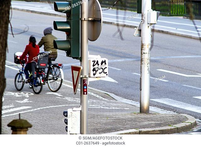 Traffic lights post and cyclists, Strasbourg, Alsace, France