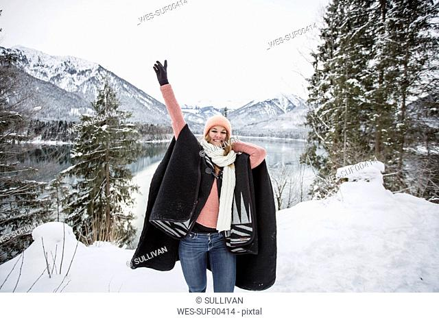Portrait of happy young woman in alpine winter landscape with lake