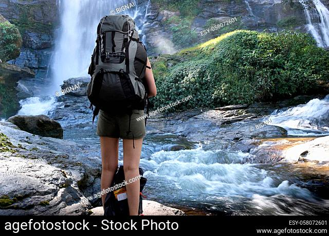Conceptual woman traveler with backpack standing look at waterfall in rain forest