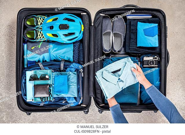 Overhead view of man's hands packing suitcase with walking boots, bike helmet, backpack, retro camera and blue shirt