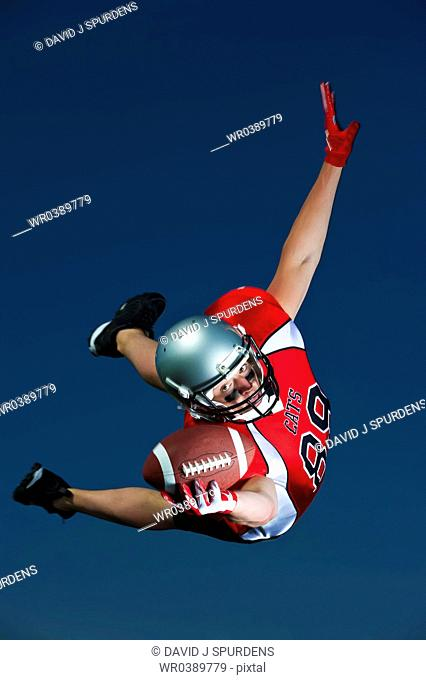 American Footballer flying through the air to make the catch