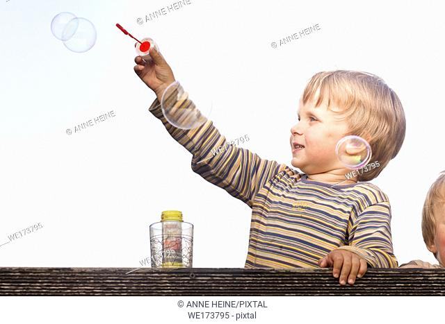 3 year old boy playing with soap bubbles. Germany