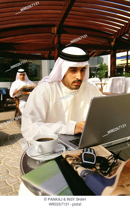 An Arab is focused at his laptop while sitting in the cafe